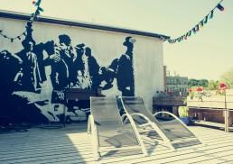 Terasoje, kuri įsikūrusi ant namo stogo, norėjome sieną papuošti piešiniu. Pažinojom Igną, kuris piešė pagal trafaretus. Išsirinkom vaizdą – mums labai tiko ir patiko Roberto Doisneau fotografija Bučinys prie Hotel de Ville. Projektoriaus pagalba perkėlėme vaizdą ant sienos ir Ignas nupurškė tokį paveikslą.